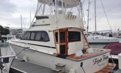 """The 37' Egg Harbor Convertible with its 14' 5"""" beam has impressive interior space with rich, teak cabinetry throughout.Triple Trouble has the most popular layout with the galley just one step down from the salon. A centerline island berth is forward and"""