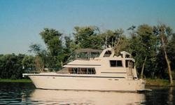 Detailed WalkthroughThis extremely spacious three-stateroom layout offers a great deal of livability and ease of access. The interior is traditional in style with its honey colored teak paneling. There are two double staterooms forward including a Kenmore