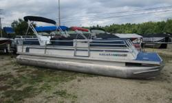 A large party barge with newer seats and bimini top. Double helm console with individual seats and covers. Powered by an Evinrude 40 hp 2 stroke motor. Beam: 8 ft. 0 in. Hull color: Blue Stock number: Jonguise Bimini top;